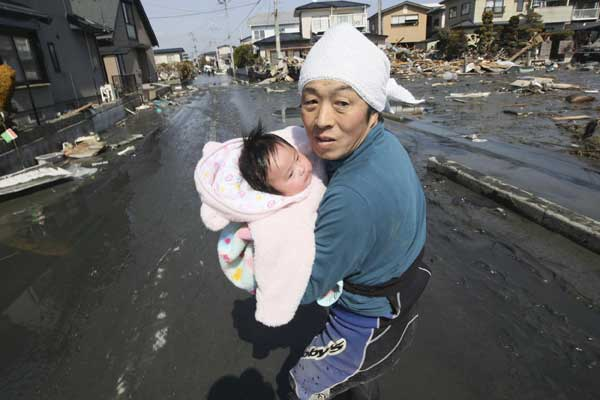 "<div class=""meta ""><span class=""caption-text "">Upon hearing another tsunami warning, a father tries to flee for safety with his just reunited four-month-old baby girl who was spotted by Japan's Self-Defense Force member in the rubble of tsunami-torn Ishinomaki Monday, March 14, 2011, three days after a powerful earthquake-triggered tsunami hit northeast Japan.  ((AP Photo/The Yomiuri Shimbun, Hiroto Sekiguchi))</span></div>"